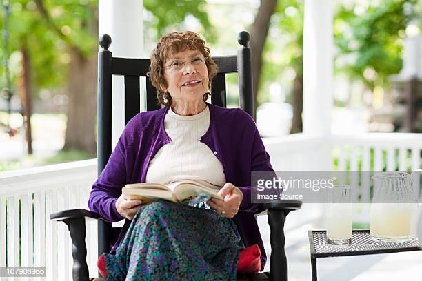 senior frau mit buch - eine seniorin allein stock-fotos und bilder