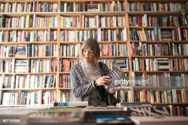 senior woman with book standing against bookshelf - book store stock photos and pictures