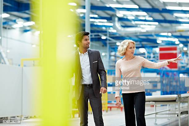 Senior woman with businessman visiting a factory