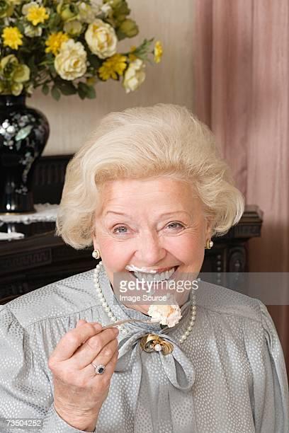 Mujer Senior con una porción de torta en la cara