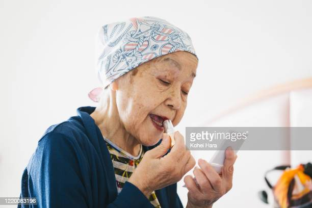 senior woman with cancer applying lipsticks to her lips - recovery stock pictures, royalty-free photos & images