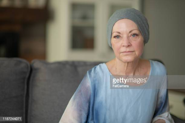 a senior woman with cancer is sitting on a couch. - headscarf stock pictures, royalty-free photos & images