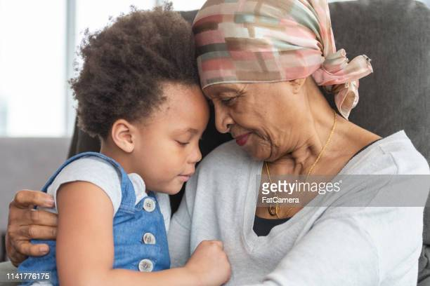 senior woman with cancer lovingly holds granddaughter - doctor's surgery stock pictures, royalty-free photos & images