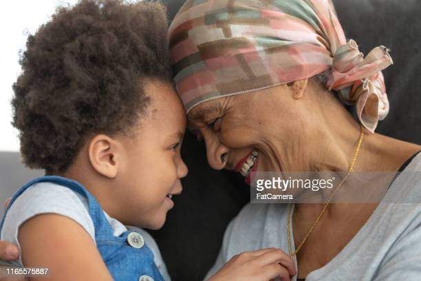 senior woman with cancer lovingly hugs granddaughter - fat granny stock pictures, royalty-free photos & images