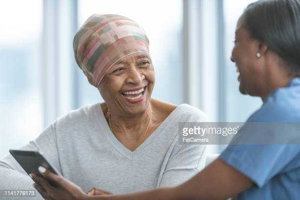 senior woman with cancer reviews test results with female doctor - cancer stock photos and pictures