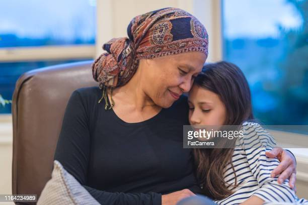 senior ethnic woman with cancer sits by her window holding her granddaughter - pacific islanders stock pictures, royalty-free photos & images