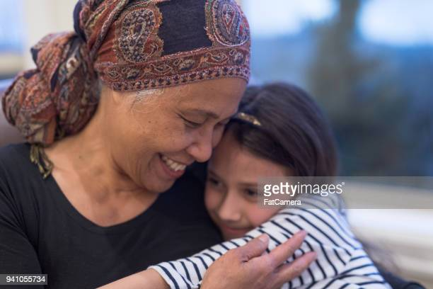 senior woman with cancer sits by her window holding her granddaughter - cancer illness stock pictures, royalty-free photos & images