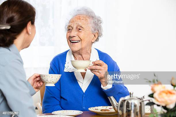 Senior woman with caregiver having cake and coffee together