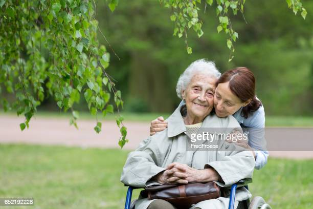 senior woman with caregiver in the park - janitorial services stock photos and pictures