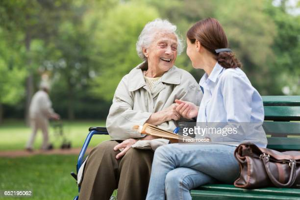 senior woman with caregiver in the park - social services stock pictures, royalty-free photos & images