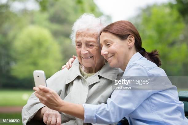 Ältere Frau mit Betreuer im park