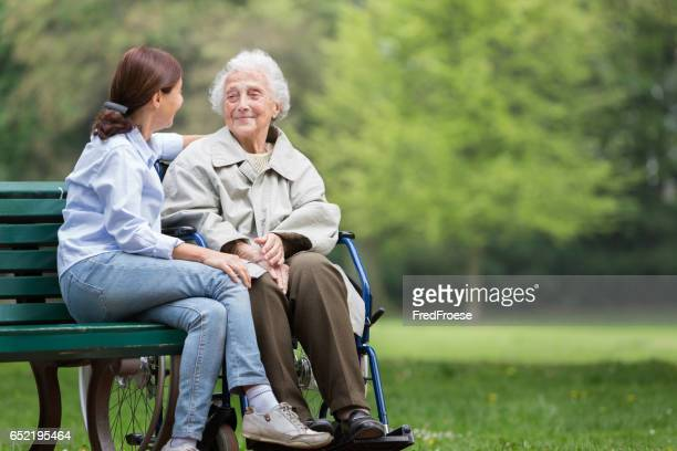 senior woman with caregiver in the park - carers stock photos and pictures
