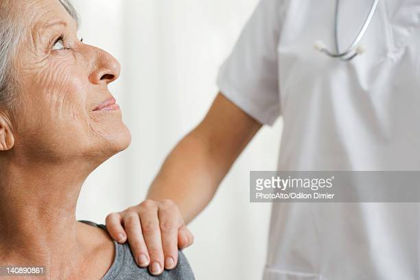 senior woman with caring doctor, cropped - hand on shoulder stock pictures, royalty-free photos & images