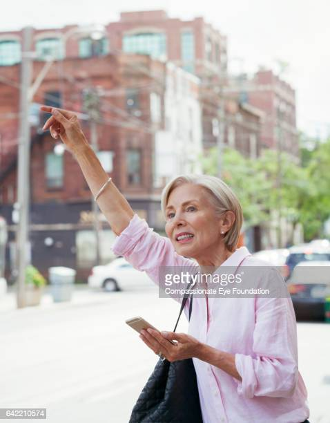 Senior woman with cell phone hailing taxi