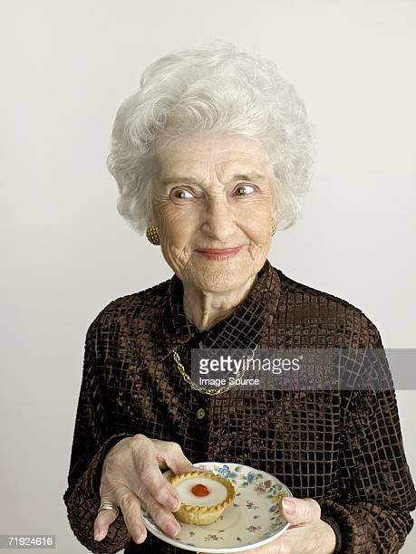senior woman with cherry bakewell tart - femme coquine photos et images de collection