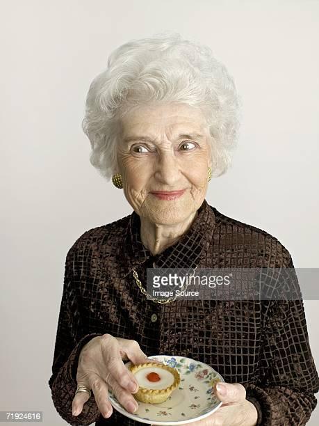 senior woman with cherry bakewell tart - cultura británica fotografías e imágenes de stock