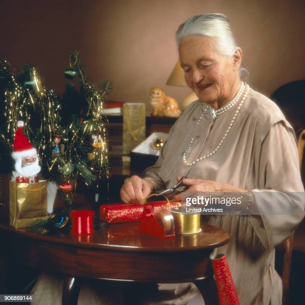 Senior woman with Christmas gifts 1980s