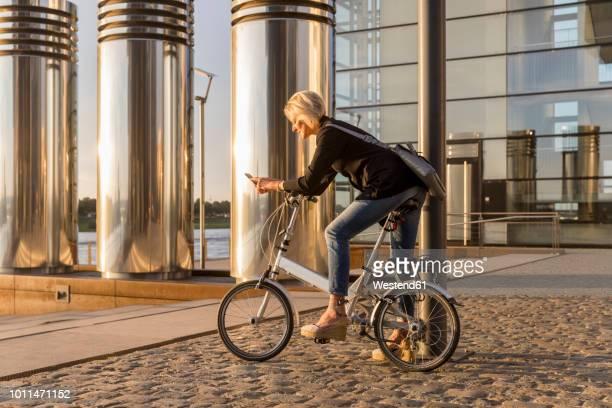 senior woman with city bike using cell phone at the riverside at sunset - colônia renânia - fotografias e filmes do acervo
