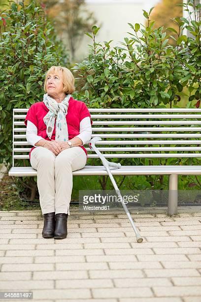 Senior woman with crutch sitting on a bench