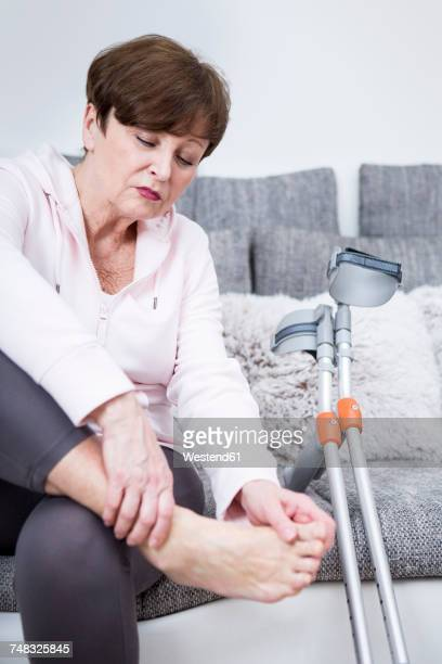 senior woman with crutches sitting on couch, checking her ankle - old lady feet stock pictures, royalty-free photos & images