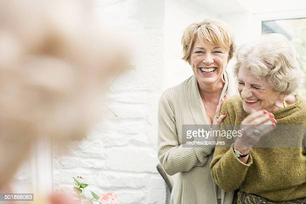 senior woman with daughter, laughing - body care stock pictures, royalty-free photos & images