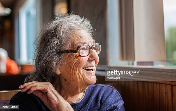 Senior Woman With Dementia Looking Out Restaurant Window