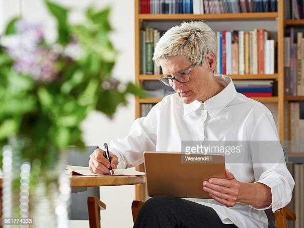 senior woman with digital tablet writing down something - down blouse stockfoto's en -beelden