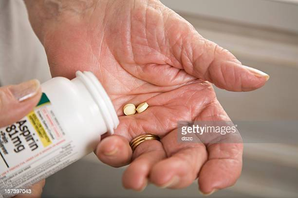 senior woman with distorted arthritis hand taking aspirin pills