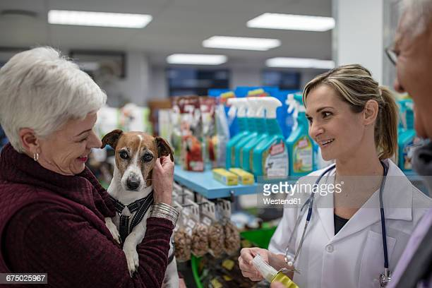 Senior woman with dog in shop at veterinarian