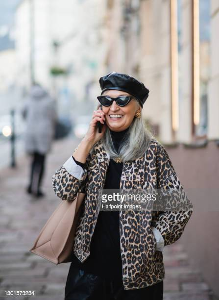 senior woman with extravagant clothes walking outdoors in town. - sunglasses stock pictures, royalty-free photos & images