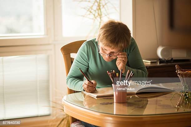 Senior Frau mit Erwachsenen Eyeglasses-Malbüchern, Europa