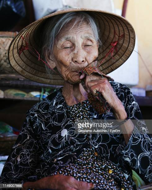 senior woman with eyes closed wearing asian style conical hat - chapeau chinois photos et images de collection