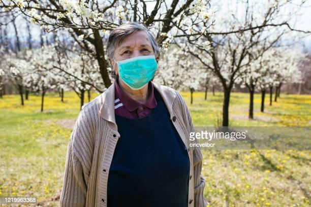 äldre kvinna med ansiktsmask stående i naturen - munskydd ensam bildbanksfoton och bilder