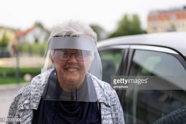 コロナウイルスロックダウン、検疫の数週間後に外出して幸せな顔の盾を持つ先輩女性 - フェイスシールド ストックフォトと画像