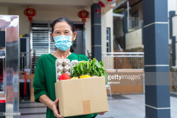 senior woman with facemask is grateful for food delivery from helpful volunteer during covid-19 - charity and relief work stock pictures, royalty-free photos & images