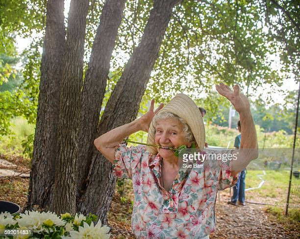 Senior woman with flower in mouth dancing on farm