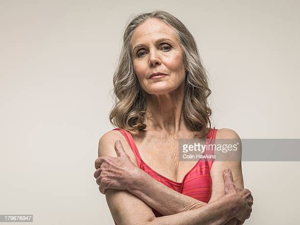 senior woman with folded arms - the ageing process stock pictures, royalty-free photos & images