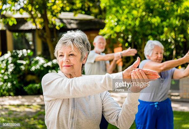 senior woman with friends exercising in yard - retirement community stock pictures, royalty-free photos & images