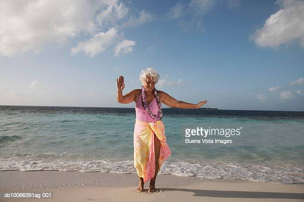 Senior woman with garland dancing on beach, smiling
