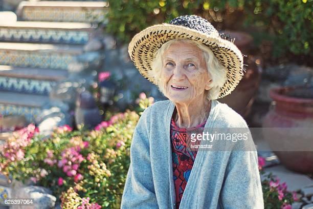 Senior Woman with Gentle Smile Relaxing in Garden