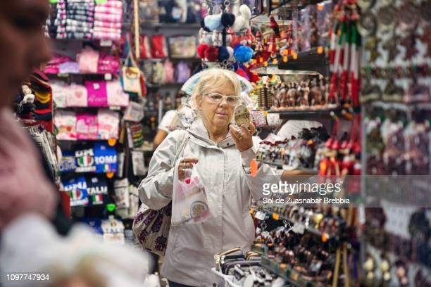 senior woman with glasses looking at herself in a mirror in a gift shop