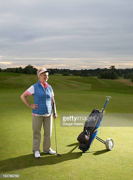 Senior woman with golf kit on golf course.