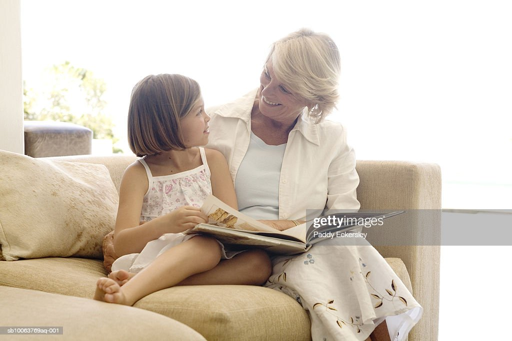 Senior woman with granddaughter (8-9) sitting on sofa, reading book : Bildbanksbilder