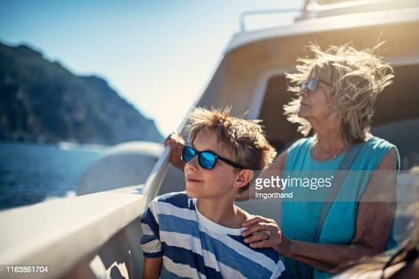 seniorin mit enkel auf dem boot in der nähe der amalfiküste, italien - passagier wasserfahrzeug stock-fotos und bilder