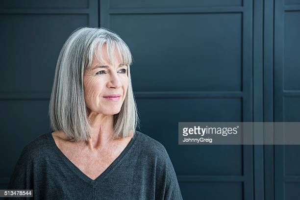 senior woman with gray hair looking away - wegkijken stockfoto's en -beelden