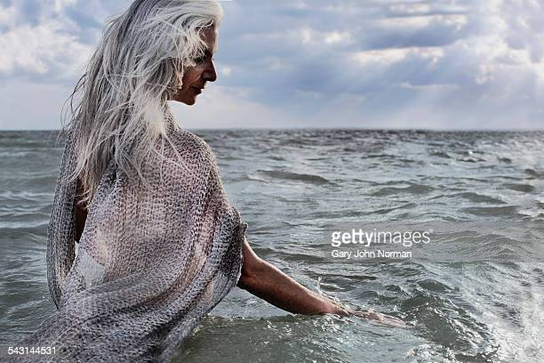 Senior woman with grey hair standing in the ocean