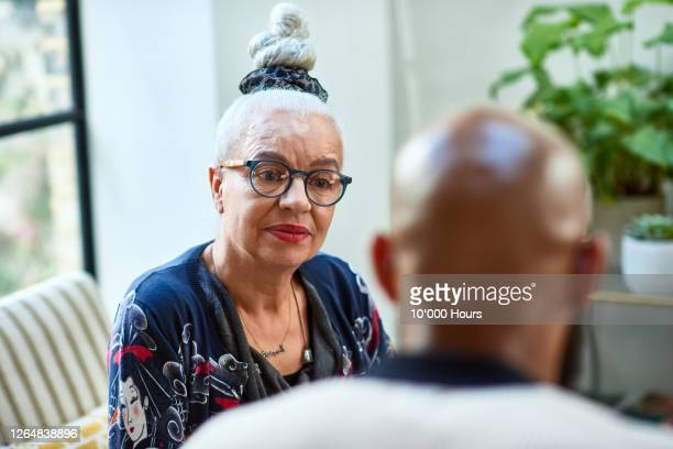 senior woman with hair bun listening to friend - mother stock pictures, royalty-free photos & images