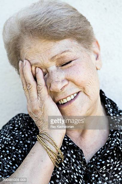Senior woman with hand against side of face