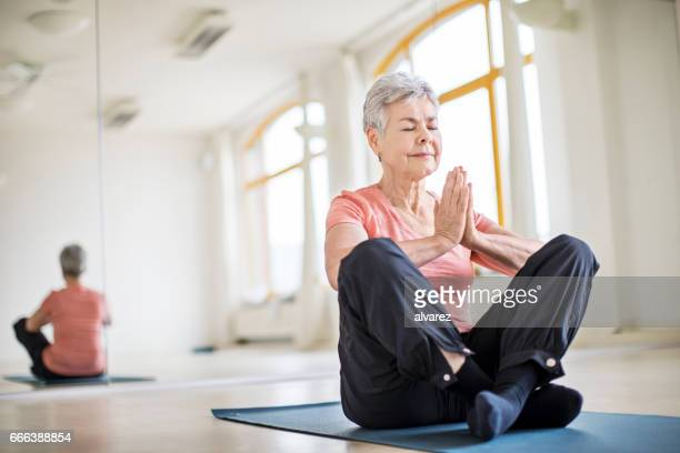 Senior woman with hands clasped doing yoga in gym