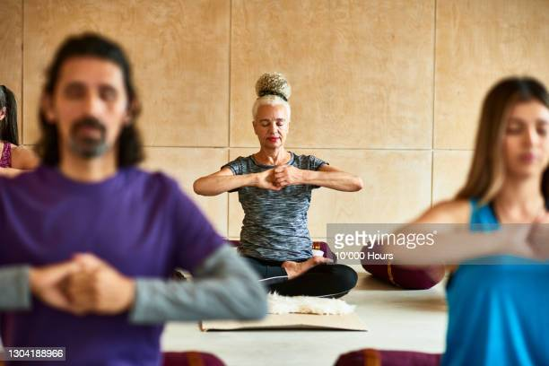 senior woman with hands clenched in yoga position - active seniors stock pictures, royalty-free photos & images